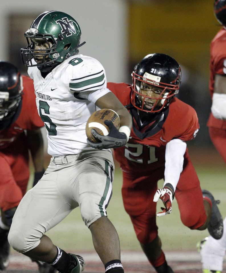 Photo - Norman North's Z'Quan Hogan gets by Del City's Brandon McFadden during the high school football game between Norman North and Del City at Del City, Okla., Friday, Sept. 13, 2013. Photo by Sarah Phipps, The Oklahoman