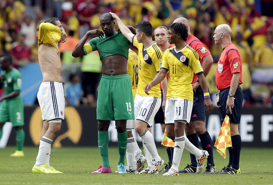 Photo - Colombia players console Ivory Coast's Yaya Toure after the group C World Cup soccer match between Colombia and Ivory Coast at the Estadio Nacional in Brasilia, Brazil, Thursday, June 19, 2014.  Colombia won the match 2-1.  (AP Photo/Marcio Jose Sanchez)