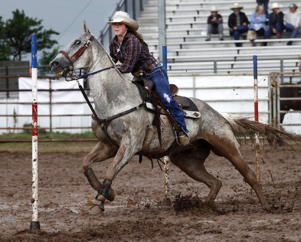 Photo - Laney Linch, Meeker, OK, competes in a muddy Pole Bending at the International Youth Finals Rodeo in Shawnee at the Heart of Oklahoma Exposition Center, Wednesday, July 9, 2014. Photo by David McDaniel, The Oklahoman