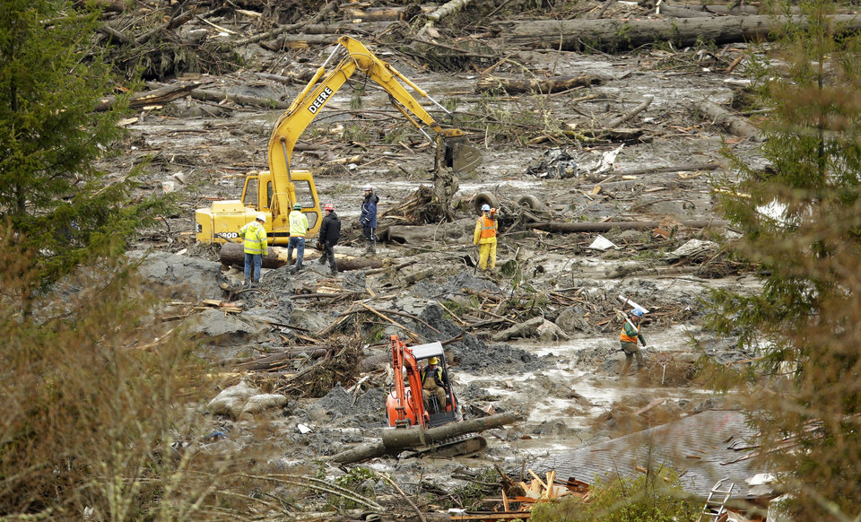 Photo - Workers use heavy equipment to clear trees and other debris, Thursday, March 27, 2014, as the search continued for victims of the massive mudslide that struck Saturday near Darrington, Wash. (AP Photo/Ted S. Warren, Pool)