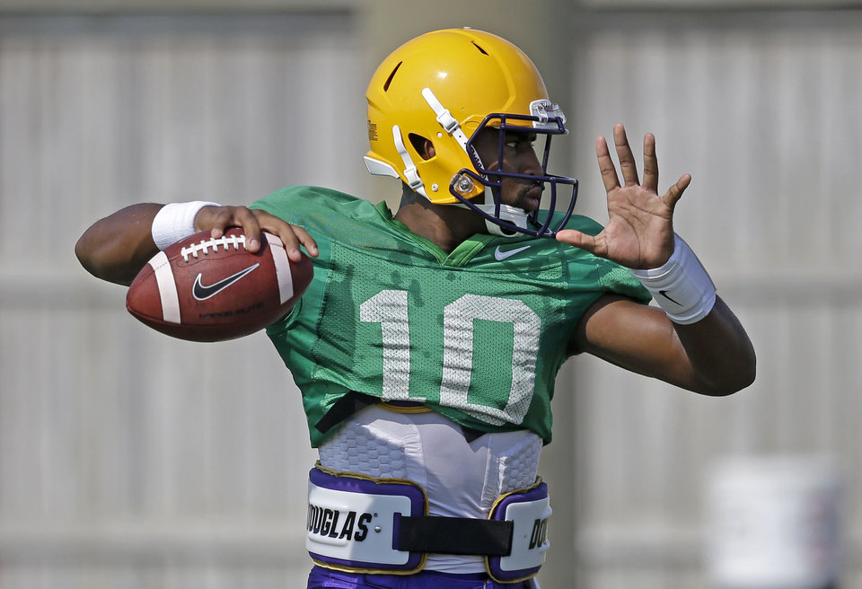 Photo - FILE - In this Aug. 6, 2014, file photo, LSU quarterback Anthony Jennings (10) passes during their NCAA college football practice in Baton Rouge, La. Tigers coach Les Miles has declared that he will use both sophomore Jennings and freshman Brandon Harris. (AP Photo/Gerald Herbert, File)