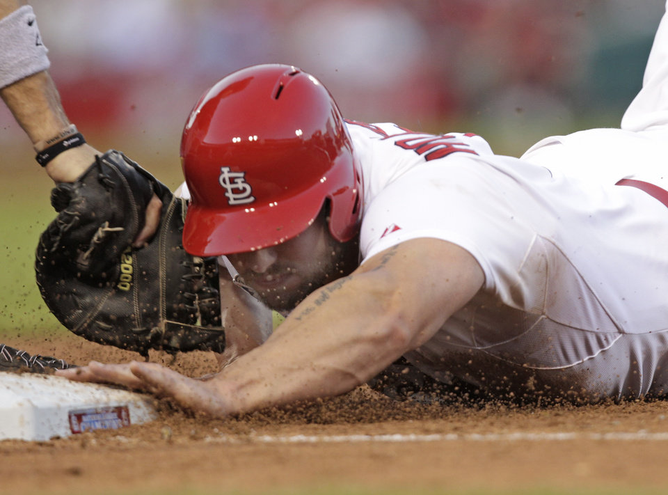 Photo - St. Louis Cardinals' Matt Holliday just beats the tag from Miami Marlins first baseman Garrett Jones while diving back to first in the sixth inning of a baseball game on Friday, July 4, 2014, in St. Louis. (AP Photo/Tom Gannam)