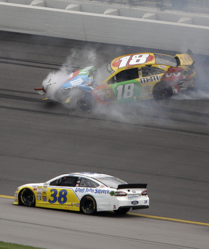 Photo - David Gilliland (38) drives past Kyle Busch's wrecked car during a NASCAR Sprint Cup series auto race at Kansas Speedway in Kansas City, Kan., Sunday, Oct. 6, 2013. (AP Photo/Charlie Riedel)