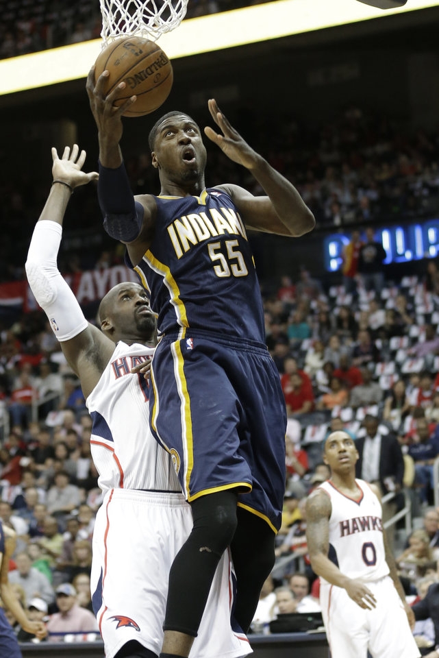 Photo - Indiana Pacers center Roy Hibbert (55) shoots over Atlanta Hawks center Johan Petro (10) during the first half in Game 4 of their first-round NBA basketball playoff series game, Monday, April 29, 2013 in Atlanta. (AP Photo/John Bazemore)