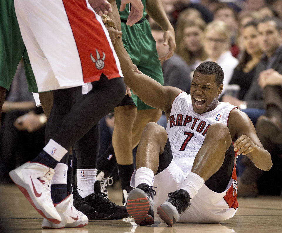 Photo - Toronto Raptors guard Kyle Lowry lets out a yell as he is helped up after hurting his ankle during first half NBA action against the Boston Celtics in Toronto on Friday March 28, 2014. (AP Photo/The Canadian Press,Frank Gunn)