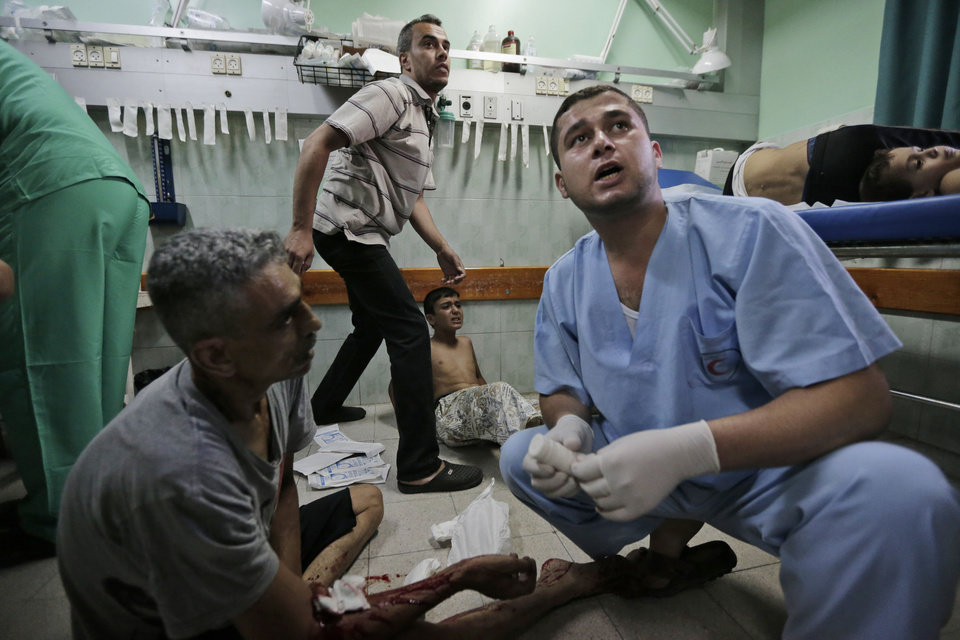 Photo - Palestinians, wounded in an Israeli strike at a house in Beit Lahiya, northern Gaza Strip, lie on the floor as they receive treatment, at the emergency room of the Kamal Adwan Hospital, in Beit Lahiya, Sunday, Aug. 3, 2014. (AP Photo/Lefteris Pitarakis)