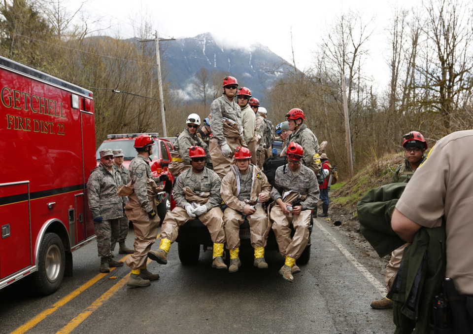 Photo - National Guard troops prepare to enter the mudslide debris on the western edge of the mudslide where it covers Highway 530 Wednesday morning, March 26, 2014 east of Oso, Wash. The debris field is laced with hazards that include fallen trees, propane and septic tanks, twisted vehicles and countless shards of shattered homes.  (AP Photo/The Herald, Mark Mulligan)   Photo taken 20140326