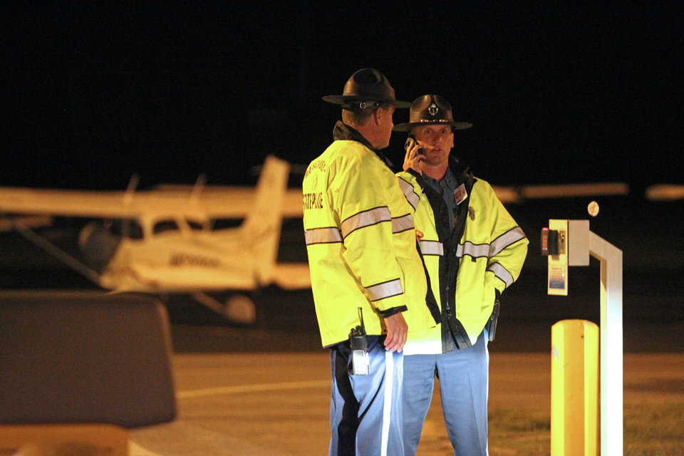 Photo - State Police stand at the gate of Hanscom Field where a private Gulfstream IV plane with seven people aboard crashed and caught fire late Saturday, May 31, 2014. (AP Photo/The Boston Herald, Stuart Cahill