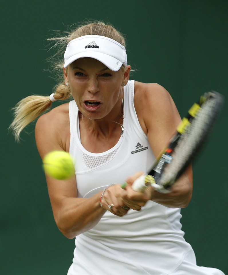 Photo - Caroline Wozniacki of Denmark plays a return to Shahar Peer of Israel during their first round match at the All England Lawn Tennis Championships in Wimbledon, London,  Monday, June  23, 2014. (AP Photo/Alastair Grant)