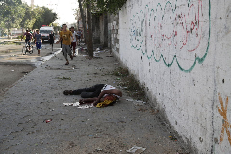 Photo - A Palestinian lays on the ground following an Israeli Strike in Shijaiyah neighborhood, eastern Gaza City, Wednesday, July 30, 2014. (AP Photo/Adel Hana)