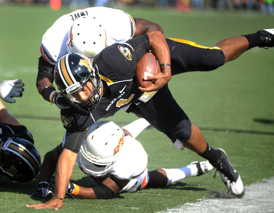 Photo - Missouri quarterback James Franklin struggles for yardage before being knocked out-of-bounds by Oklahoma State cornerback Brodrick Brown, bottom, and safety Daytawion Lowe, top, during the first half of an NCAA college football game, Saturday, Oct. 22, 2011, in Columbia, Mo. (AP Photo/L.G. Patterson)