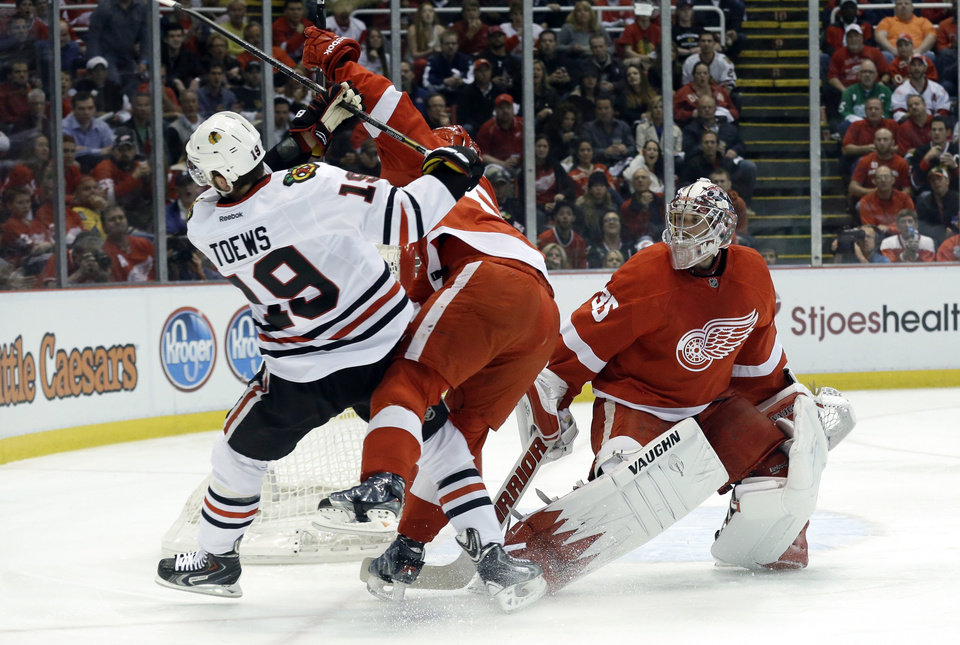 Photo - Detroit Red Wings defenseman Niklas Kronwall, center, of Sweden, checks Chicago Blackhawks center Jonathan Toews (19) away from goalie Jimmy Howard (35) during the first period in Game 4 of the Western Conference semifinals in the NHL hockey Stanley Cup playoffs in Detroit, Thursday, May 23, 2013. (AP Photo/Paul Sancya)