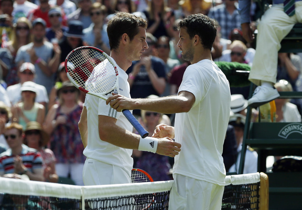 Photo - Grigor Dimitrov of Bulgaria, right, shakes hands with defending champion Andy Murray of Britain after defeating him in their men's singles quarterfinal match at the All England Lawn Tennis Championships in Wimbledon, London, Wednesday July 2, 2014. (AP Photo/Pavel Golovkin)