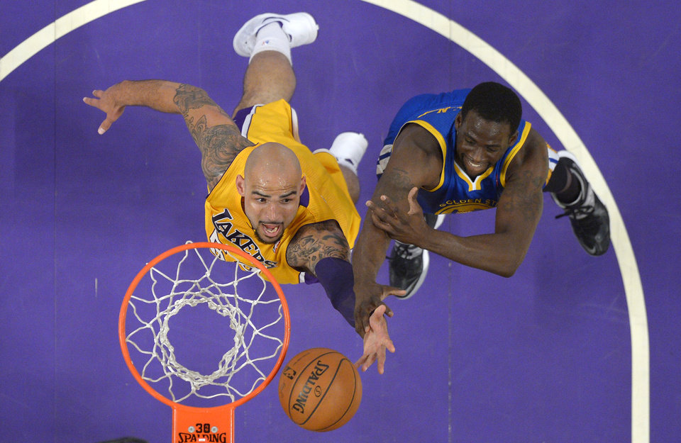 Photo - Los Angeles Lakers center Robert Sacre, left, shoots as Golden State Warriors forward Draymond Green defends during the first half of an NBA basketball game, Friday, April 11, 2014, in Los Angeles. (AP Photo/Mark J. Terrill)