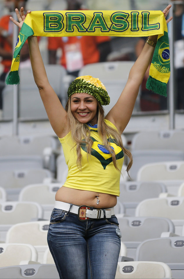 Photo - A Brazil supporter holds a Brazil scarf prior to the World Cup semifinal soccer match between Brazil and Germany at the Mineirao Stadium in Belo Horizonte, Brazil, Tuesday, July 8, 2014. (AP Photo/Frank Augstein)