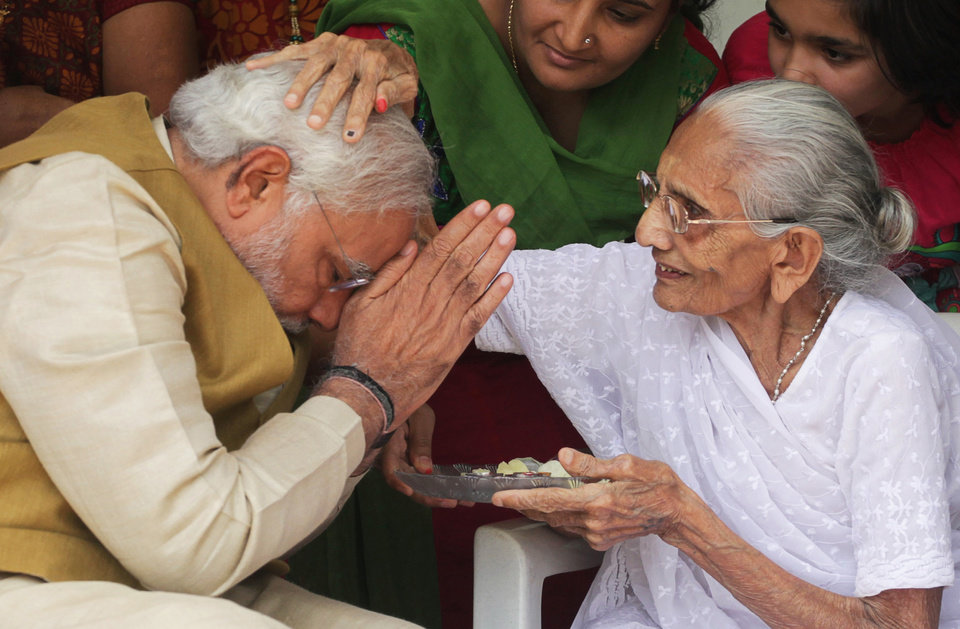 Photo - 90-year-old Hiraben blesses her son and India's next prime minister Narendra Modi at her home in Gandhinagar, in the western Indian state of Gujarat, Friday, May 16, 2014. The top official in Gujarat state for over a decade, Modi often contrasted his humble roots with the posh background of his main rival, 43-year-old Rahul Gandhi, heir to India's most powerful political dynasty. As the career politician led his party through a dazzling, high-tech election campaign, Modi called voters' attention to his mother riding a three-wheeled auto-rickshaw to cast her ballot earlier this month.