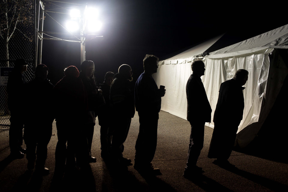Photo -   Under the lights of a generator, voters wait in line outside of a tent serving as a polling site in the Midland Beach section of Staten Island, New York, on Election Day Tuesday, Nov. 6, 2012. The original polling site, a school, was damaged by Superstorm Sandy. (AP Photo/Seth Wenig)