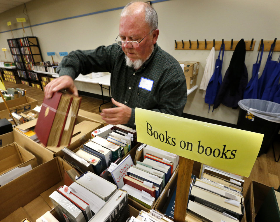 Photo -  Kris Lackey gets books ready for the Friends of the Norman Library's Better Books Sale that opens Friday and continues through Sunday. PHOTO BY STEVE SISNEY, THE OKLAHOMAN   STEVE SISNEY -