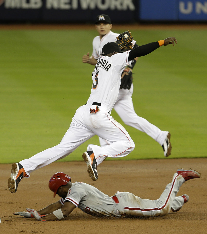 Photo - Philadelphia Phillies' Jimmy Rollins, bottom, safely steals second base as Miami Marlins shortstop Adeiny Hechavarria (3) leaps to avoid Rollins in the first inning of a baseball game in Miami, Tuesday, May 20, 2014. (AP Photo/Alan Diaz)