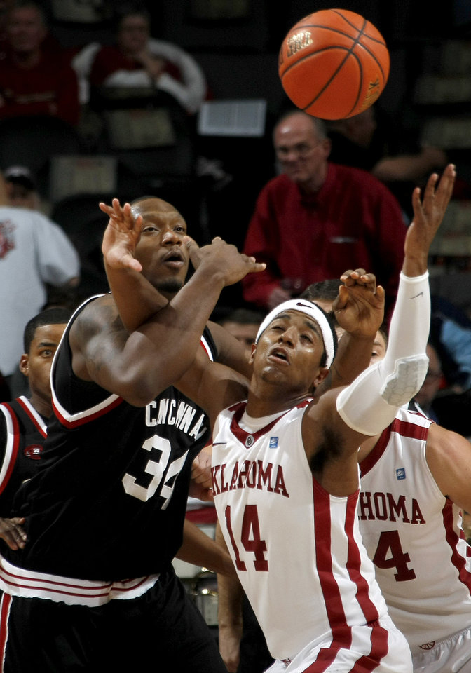 Photo - OU's Carl Blair Jr. goes for the ball beside Cincinnati's Yancy Gates during the All-College Classic basketball game between the University of Oklahoma and Cincinnati at the Oklahoma City Arena on Saturday, December 18,  2010.   Photo by Bryan Terry, The Oklahoman