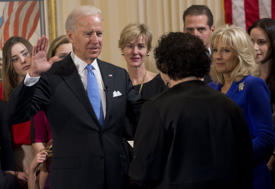 Photo - Vice President Joe Biden takes the oath of office during the 57th Presidential Inauguration official swearing-in ceremony at the Naval Observatory on Sunday, January 20, 2013 in Washington. The oath is administered by US Supreme Court Justice Sonia Sotomayor as Dr. Jill Biden, right, looks on. (AP Photo/Saul Loeb, Pool)