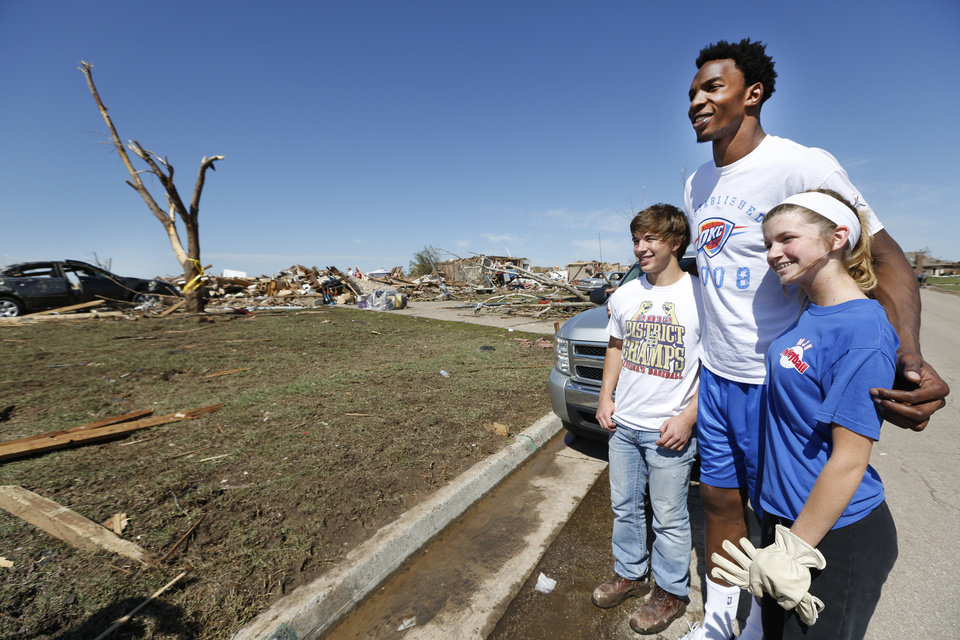 Oklahoma City Thunder\'s Hasheem Thabeet, center, poses for a photo with Jared Ledbetter and Samantha Balak near SW 144th and Robinson in Oklahoma City, Wednesday May 22, 2013. Members of the Oklahoma City Thunder and family members took a tour of the area hit by a tornado on Monday afternoon. Photo By Steve Gooch, The Oklahoman