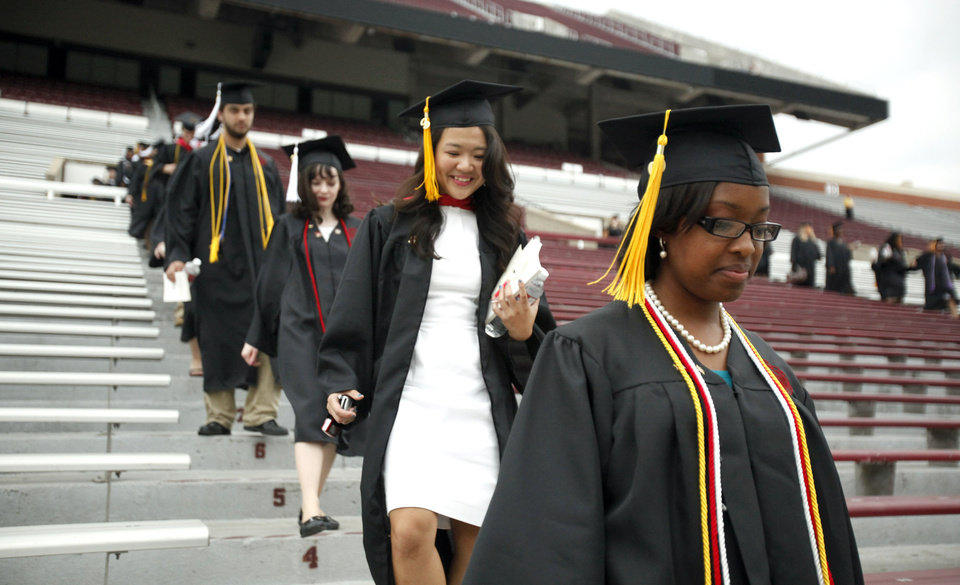 Photo - Graduates walk during the 2009 University of Oklahoma Commencement at the Gaylord Family - Oklahoma Memorial Stadium, Friday, May 15, 2009, in Norman, Okla. Photo by Sarah Phipps, The Oklahoman