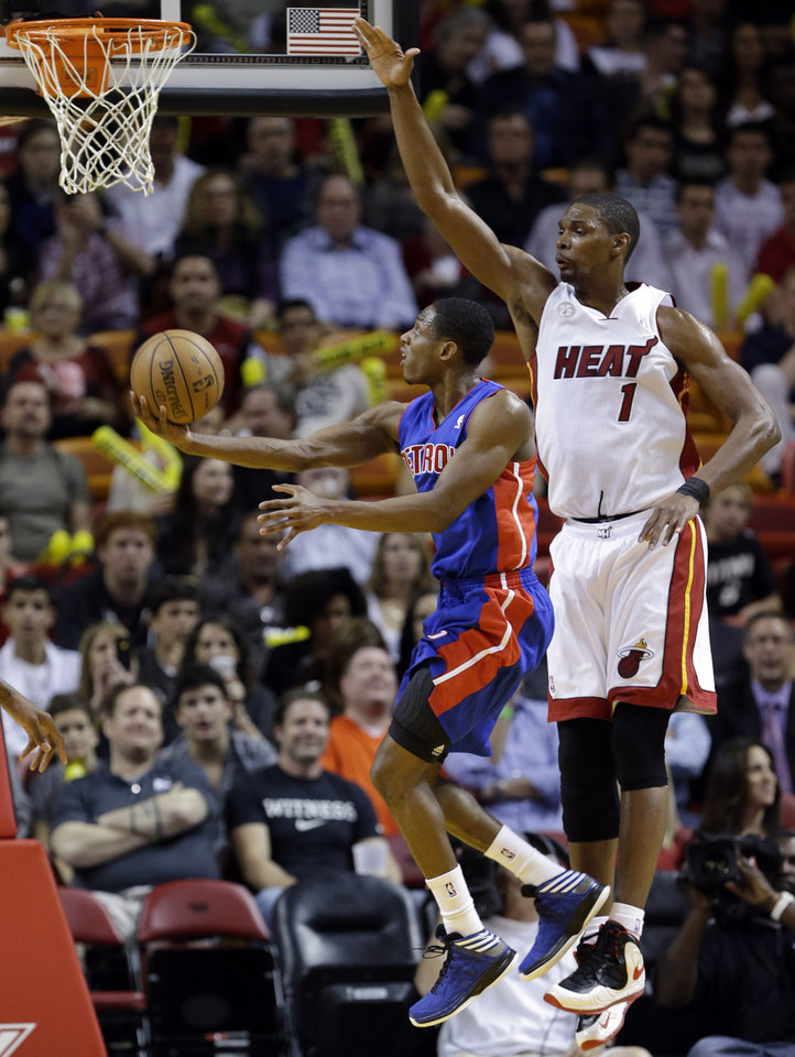 Photo - Detroit Pistons guard Brandon Knight goes up for a shot against Miami Heat center Chris Bosh (1) during the first half of an NBA basketball game, Friday, Jan. 25, 2013 in Miami. (AP Photo/Wilfredo Lee)
