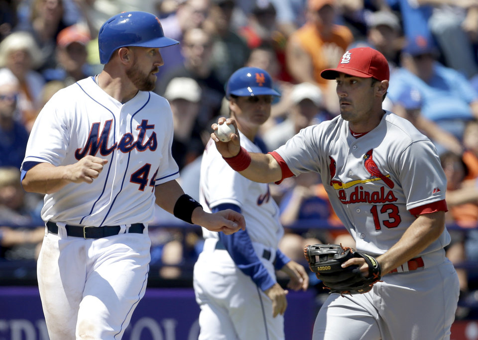 Photo - New York Mets' John Buck, left, is tagged out by St. Louis Cardinals third baseman Matt Carpenter after being caught between third and home during the fourth inning of an exhibition spring training baseball game, Friday, March 29, 2013, in Port St. Lucie, Fla. (AP Photo/Jeff Roberson)