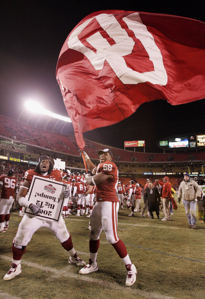 Photo - CELEBRATE, CELEBRATION: Oklahoma's George Robinson (72) and Carl Pendleton (68) wave the Sooner flag as the team celebrates after the 21-7 win over the Huskers in the Big 12 Championship game during the University of Oklahoma Sooners (OU) college football game against the University of Nebraska Cornhuskers (NU) at Arrowhead Stadium, on Saturday, Dec. 2, 2006, in Kansas City, Mo.   by Chris Landsberger, The Oklahoman  ORG XMIT: KOD