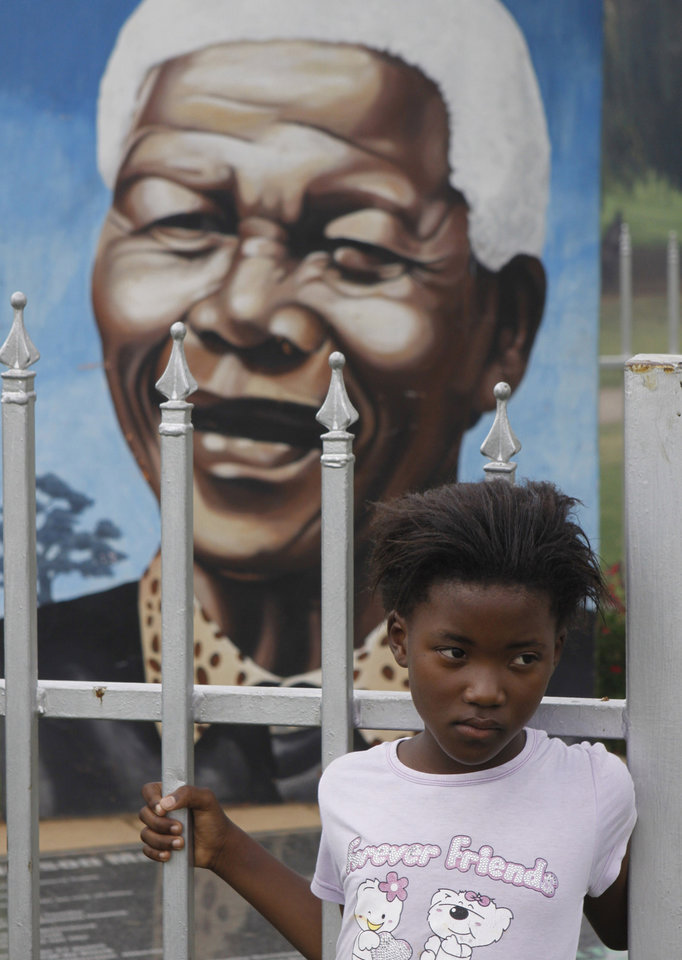 A child stands in front of a portrait of former president Nelson Mandela in a Park in Soweto, South Africa, Thursday, March, 28, 2013. 94-year-old Mandela, the anti-apartheid leader who became South Africa\'s first black president, has been hit by a lung infection again and is in a hospital, the presidency said. Mandela, has become increasingly frail in recent years and has been hospitalized several times in recent months, including earlier this month when he underwent what authorities said was a scheduled medical test. The Nobel laureate is a revered figure in South Africa, which has honored his legacy of reconciliation by naming buildings and other places after him and printing his image on national banknotes. (AP Photo/Denis Farrell)