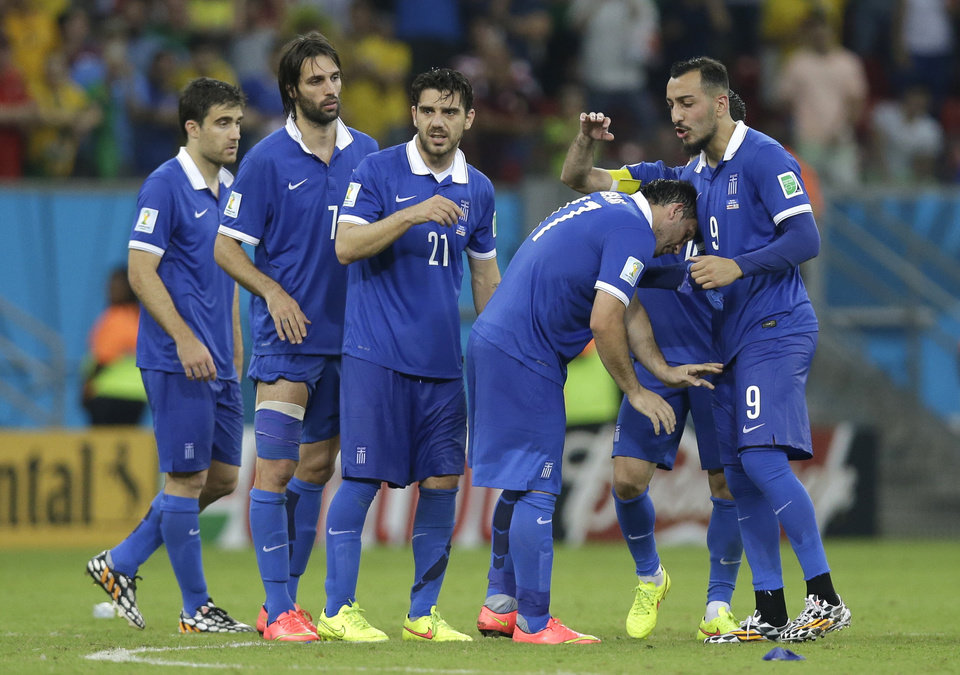Photo - Greece's Fanis Gekas, second right, is consoled after missing a kick during a penalty shootout at the end of the World Cup round of 16 soccer match between Costa Rica and Greece at the Arena Pernambuco in Recife, Brazil, Sunday, June 29, 2014. Costa Rica won 5-3 on penalties after the match ended 1-1. (AP Photo/Andrew Medichini)