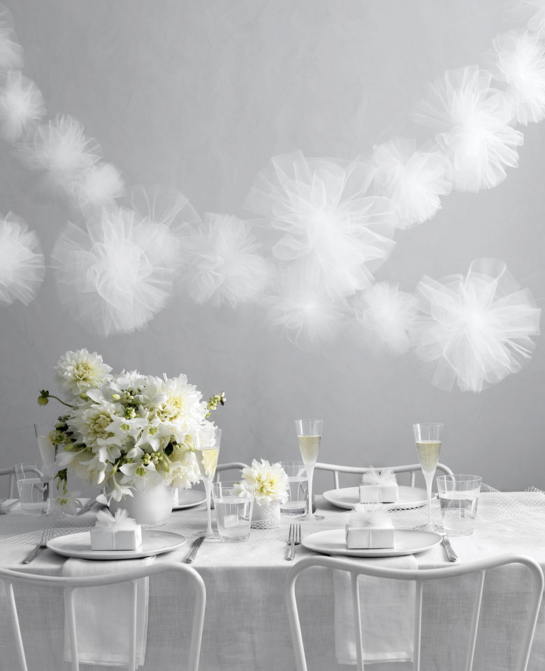Photo - This undated photo courtesy of Raymond Ham shows a table decorated using mostly white. This image was originally published in the Winter 2010 issue of Martha Stewart Weddings magazine. White is the traditional color for brides, but many of them are surrounding themselves with white way beyond a head-to-toe look. It's more like left to right and floor to ceiling, and everything in between.   (AP Photo/Raymond Hom)