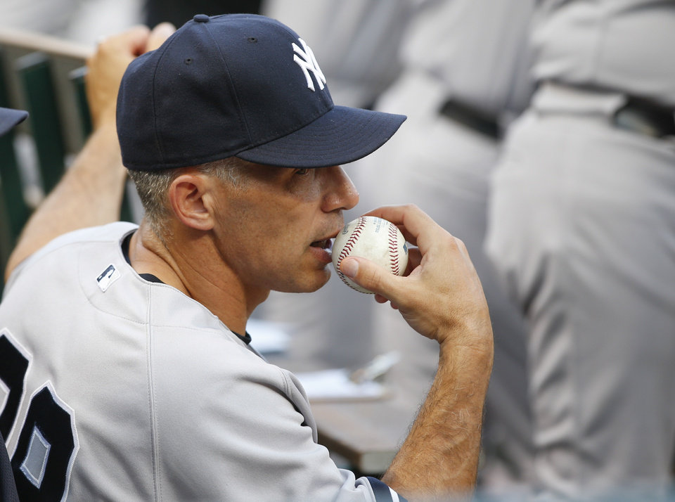 Photo - New York Yankees manager Joe Girardi watches from the dugout during the Yankees' baseball game against the Texas Rangers, Wednesday, July 24, 2013, in Arlington, Texas. (AP Photo/Jim Cowsert)