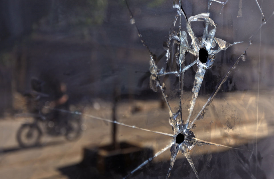 Photo -   FILE - In a Tuesday, June 5, 2012 file photo, a Syrian man on a motorcycle is seen reflected in the glass door of a shop which has bullet holes, in the town of Taftanaz, 15 kilometers east of Idlib, Syria. At dawn on April 3, Syrian forces shelled the town in the first volley of what residents say was a massive assault after a string of large protests calling for the end of the autocratic rule of President Bashar Assad. (AP Photo)