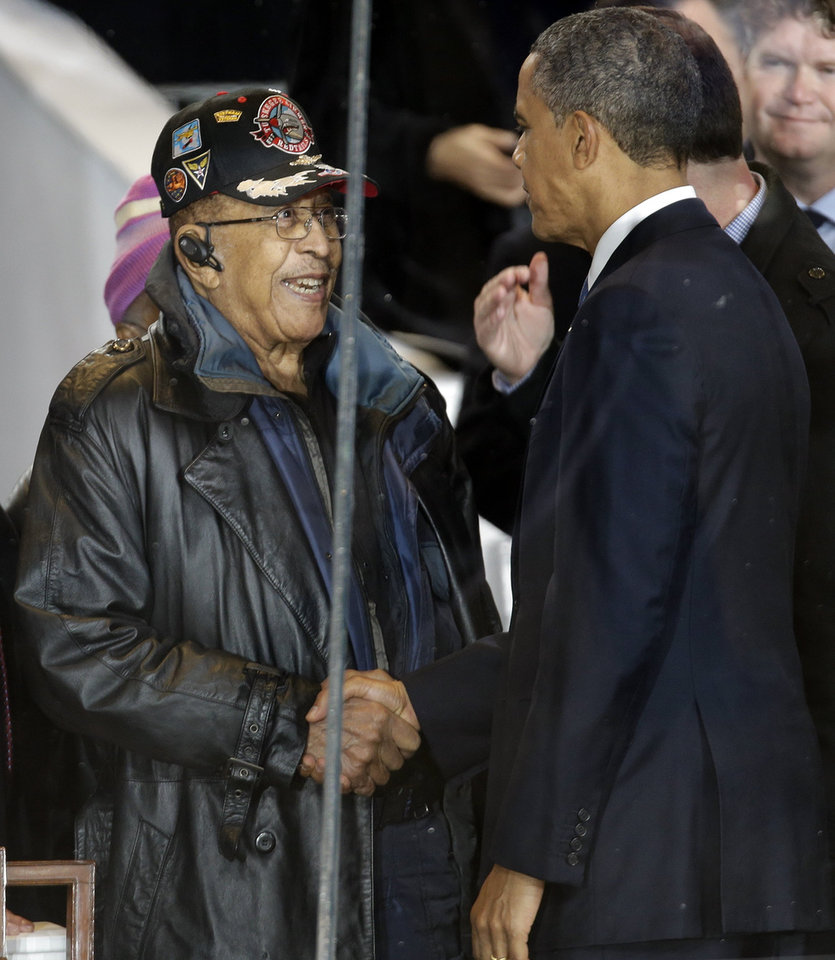 Photo - President Barack Obama speaks to a former member of the Tuskegee airman in the presidential box during the inaugural parade, Monday, Jan. 21, 2013, in Washington. Thousands  marched during the 57th Presidential Inauguration parade after the ceremonial swearing-in of President Barack Obama. (AP Photo/Gerald Herbert) ORG XMIT: DCMS167