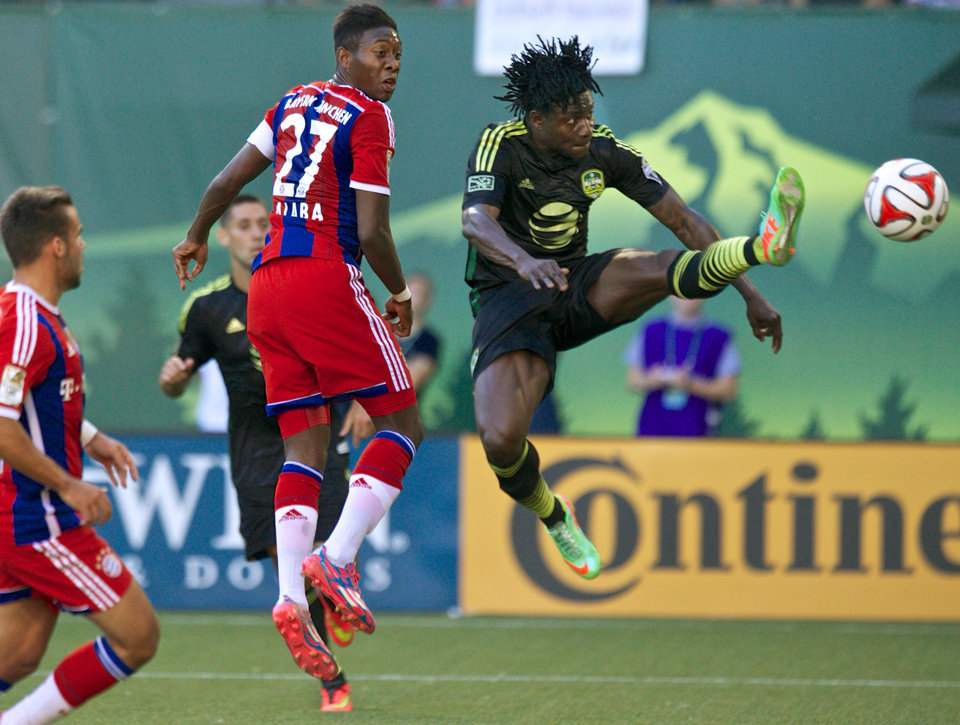 Photo - MLS All-Stars forward Obafemi Martins, right, of the Seattle Sounders, takes a shot against Bayern Munich during the MLS All-Star soccer game, Wednesday, Aug. 6, 2014, in Portland, Ore. (AP Photo/The Oregonian, Thomas Boyd)