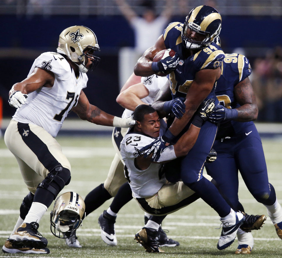St. Louis Rams defensive end Robert Quinn (94) is pulled down by New Orleans Saints running back Pierre Thomas, center, after recovering a fumble as Saints' Charles Brown, left, watches during the third quarter of an NFL football game Sunday, Dec. 15, 2013, in St. Louis. (AP Photo/Charles Rex Arbogast)