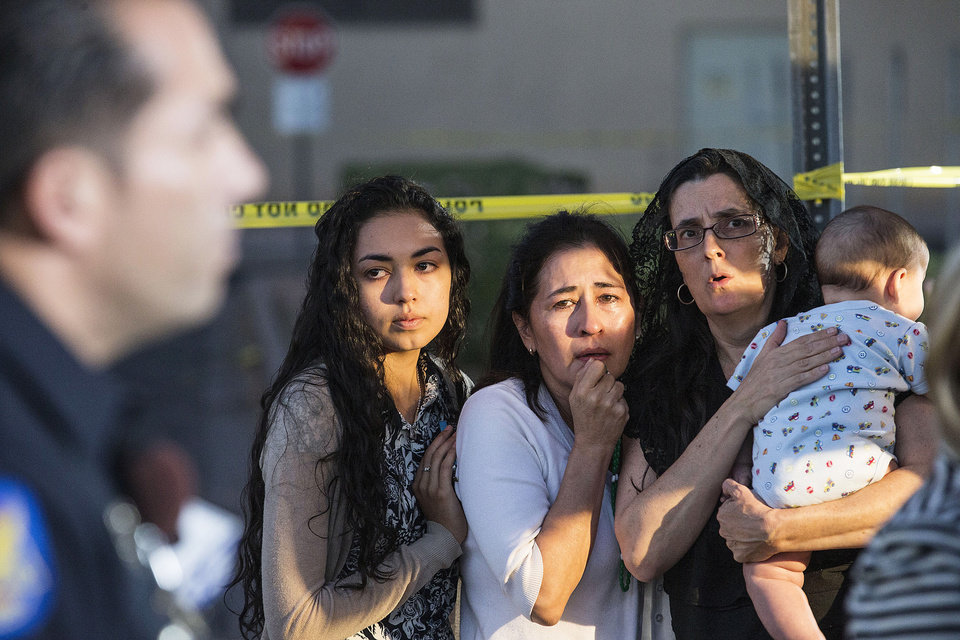 Photo - Mater Misericordiae (Mother of Mercy) Mission, church members, from left,  Kirsten Duarte,  her mother Theresa Duarte,   and Mary Langlois, cry while listening to Phoenix Police during a news conference on Wednesday, June 11, 2014.  Police say one priest was shot to death and another is injured after an attack at the church in downtown Phoenix. The Roman Catholic Diocese of Phoenix on Thursday identified the slain priest as the Rev. Kenneth Walker and the injured priest as the Rev. Joseph Terra. (AP Photo/The Arizona Republic, Nick Oza)  MARICOPA COUNTY OUT; MAGS OUT; NO SALES