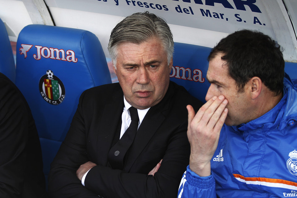 Photo - Real's coach Carlo Ancelotti talks with a colleague before a Spanish La Liga soccer match between Real Madrid and Getafe at the Coliseum Alfonso Perez stadium in Madrid, Spain, Sunday, Feb. 16, 2014. (AP Photo/Gabriel Pecot)