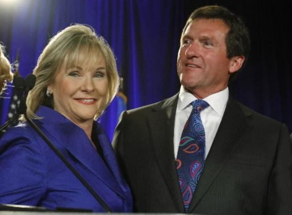 Photo - Oklahoma Governor-elect  Mary  Fallin, left, stands with her husband, Wade Christensen, right, at a victory party in Oklahoma City, Tuesday, Nov. 2, 2010.  (AP Photo/Sue Ogrocki)