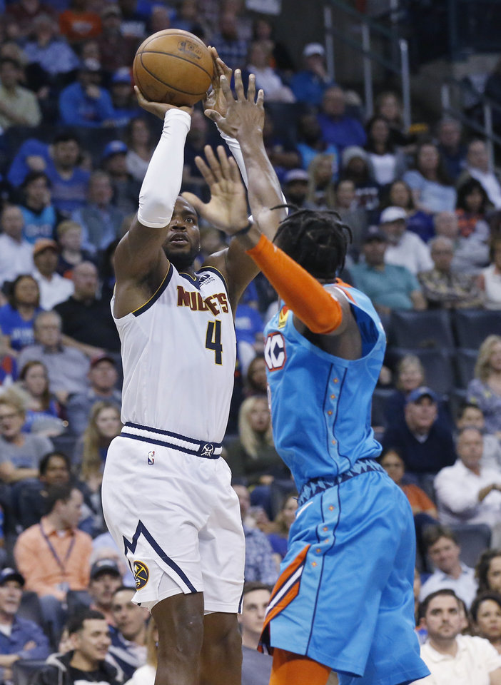 Photo - Denver Nuggets forward Paul Millsap (4) shoots as Oklahoma City Thunder forward Jerami Grant, right, defends in the first half of an NBA basketball game Friday, March 29, 2019, in Oklahoma City. (AP Photo/Sue Ogrocki)