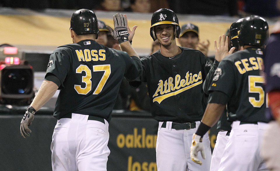 Photo -   Oakland Athletics' Brandon Moss (37) is congratulated after hitting a two-run home run off Boston Red Sox's Alfredo Aceves in the inning of a baseball game Friday, Aug. 31, 2012, in Oakland, Calif. (AP Photo/Ben Margot)