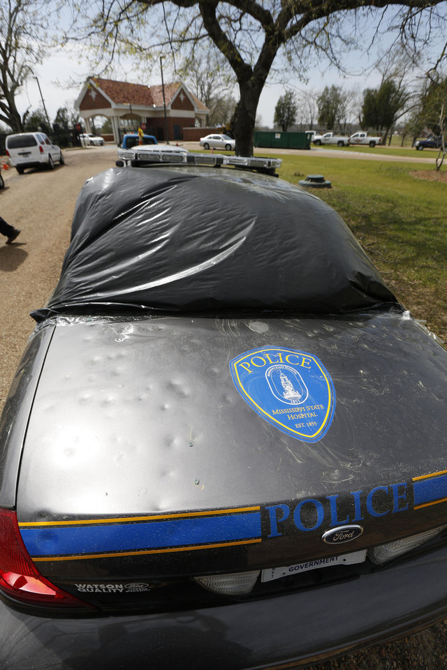Photo - This police car at Mississippi's primary psychiatric hospital is secured in plastic after Monday's hail storm in Whitfield, Miss., Thursday, March 21, 2013. Workmen are throughout the 350-acre campus as they race to finish preliminary repairs before another wave of severe weather strikes this weekend. An official estimates this week's hail storm damage could exceed $1 million for the hospital and a nearby facility for people with developmental disabilities. (AP Photo/Rogelio V. Solis)