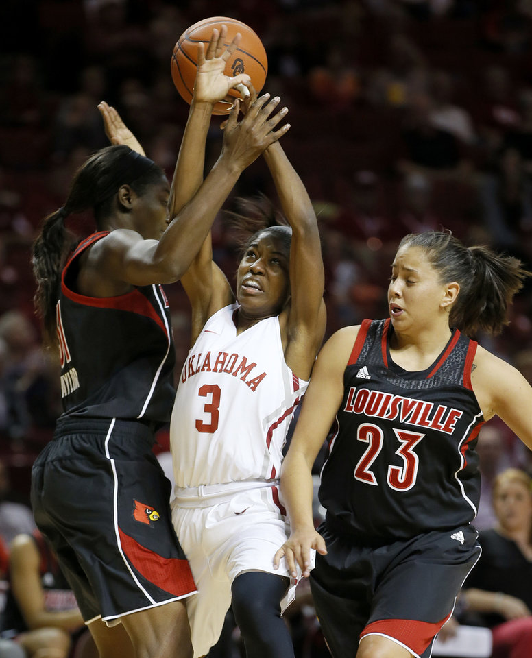 Photo - Oklahoma's Aaryn Ellenberg (3) goes between Louisville's Asia Taylor, left, and Shoni Schimmel (23) during the first half of an NCAA college basketball game in Norman, Okla., Sunday, Nov. 17, 2013. (AP Photo/Bryan Terry)