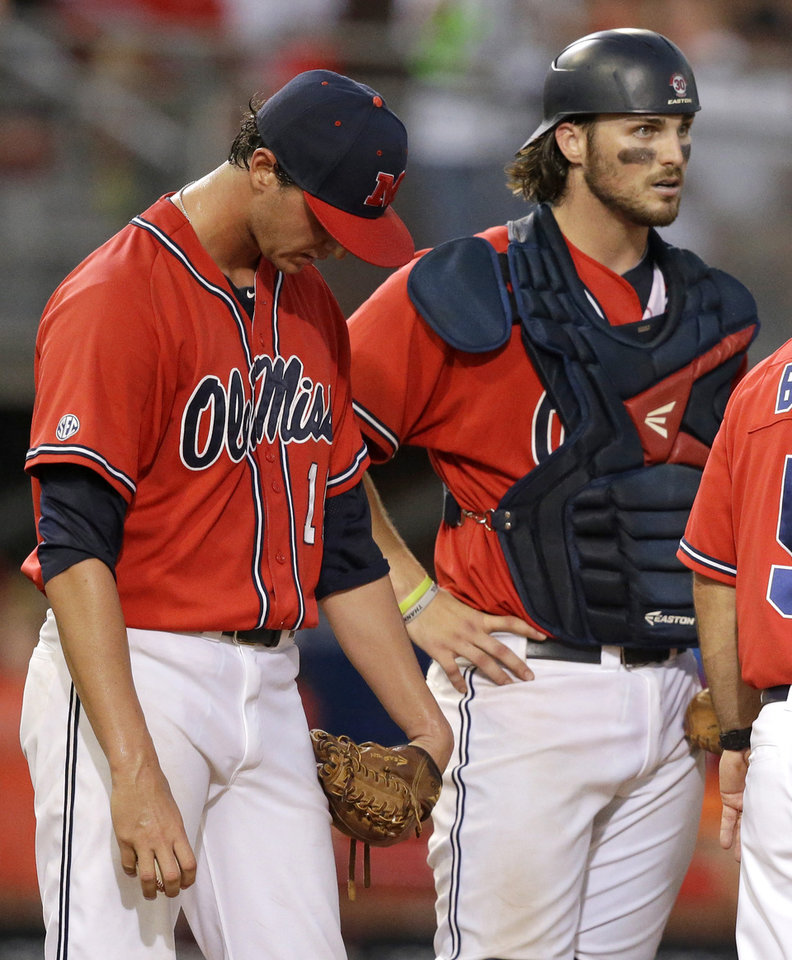 Photo - Mississippi pitcher Chris Ellis (10) reacts with catcher Will Allen (30) after giving up a three run home run in the third inning of an NCAA college baseball tournament super regional game against Louisiana Lafayette in Lafayette, La., Saturday, June 7, 2014. (AP Photo/Gerald Herbert)