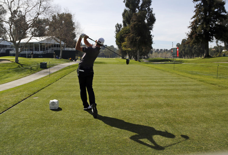 Photo - Defending champion John Merrick hits from the 15th tee during the pro-am of the Northern Trust Open golf tournament at Riviera Country Club in the Pacific Palisades area of Los Angeles on Wednesday, Feb. 12, 2014.  (AP Photo/Reed Saxon)