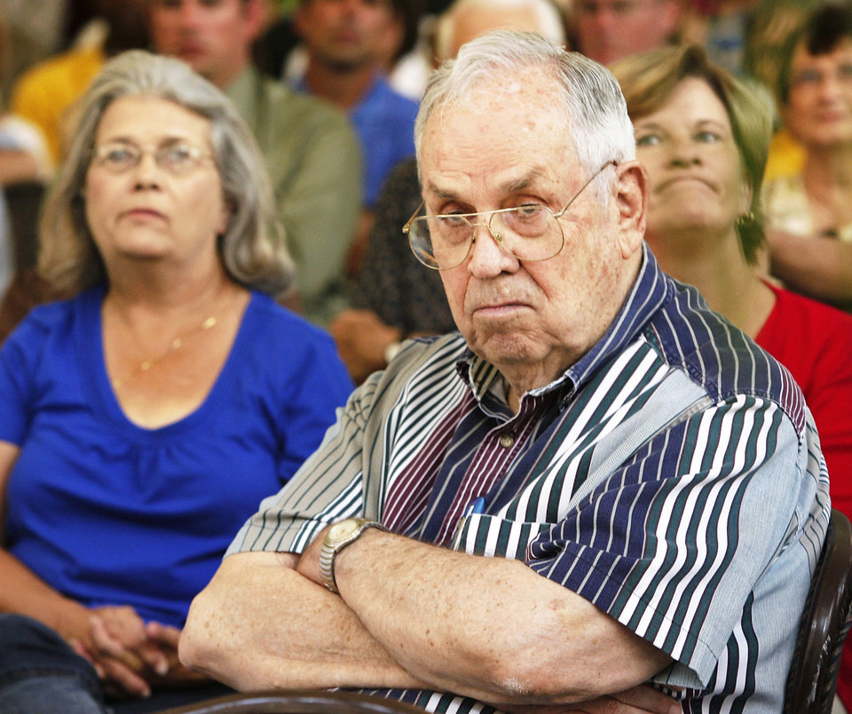 Photo - Rense Johnson,  president of the grassroots organization Citizens for Term Limits, listens to Coburn speak Monday.