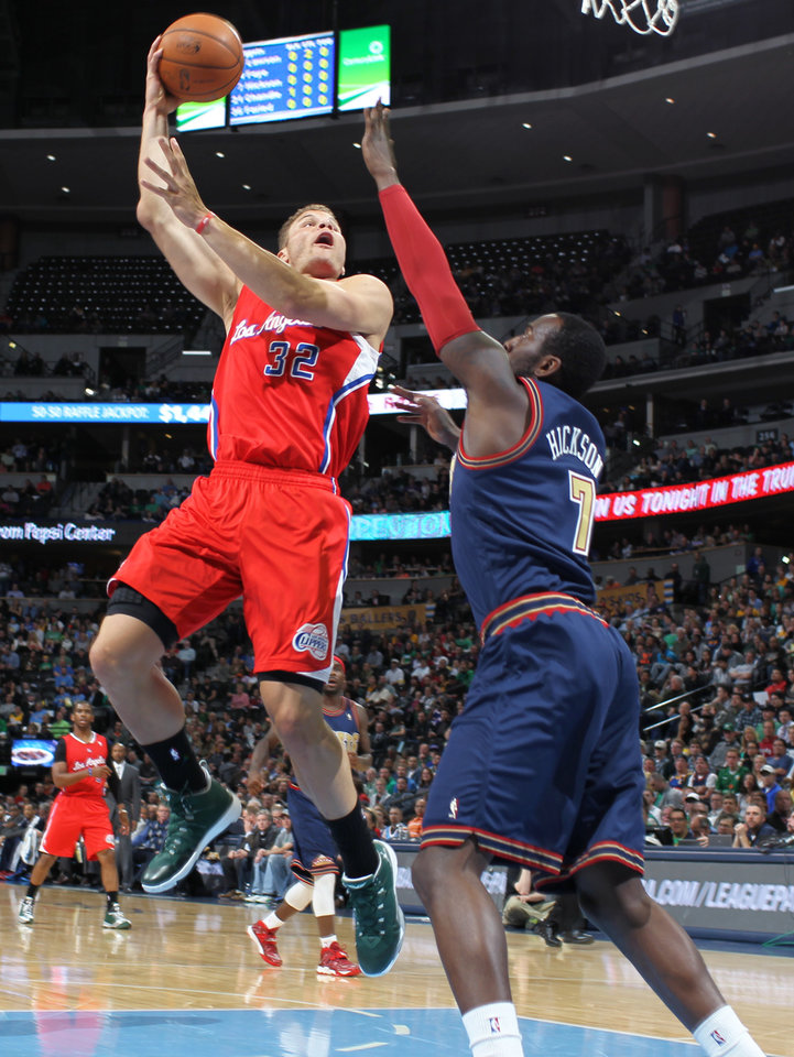 Photo - Los Angeles Clippers forward Blake Griffin, left, flies through lane to make a hook shot for a basket over Denver Nuggets forward J.J. Hickson in the first quarter of an NBA basketball game in Denver on Monday, March 17, 2014. (AP Photo/David Zalubowski)