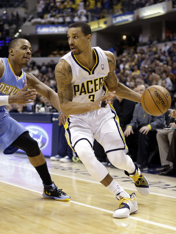 Photo - Indiana Pacers guard George Hill, right, drives on Denver Nuggets guard Randy Foye in the second half of an NBA basketball game in Indianapolis, Monday, Feb. 10, 2014. The Pacers won 119-80. (AP Photo/Michael Conroy)